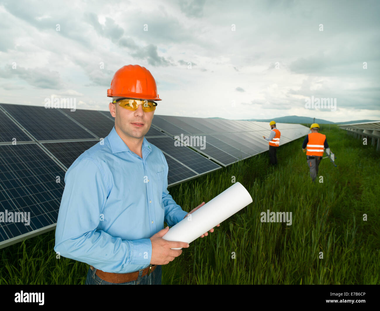 Male engineer wearing protection equipment standing in solar panel male engineer wearing protection equipment standing in solar panel station holding blueprints with two other workers in backg malvernweather Choice Image