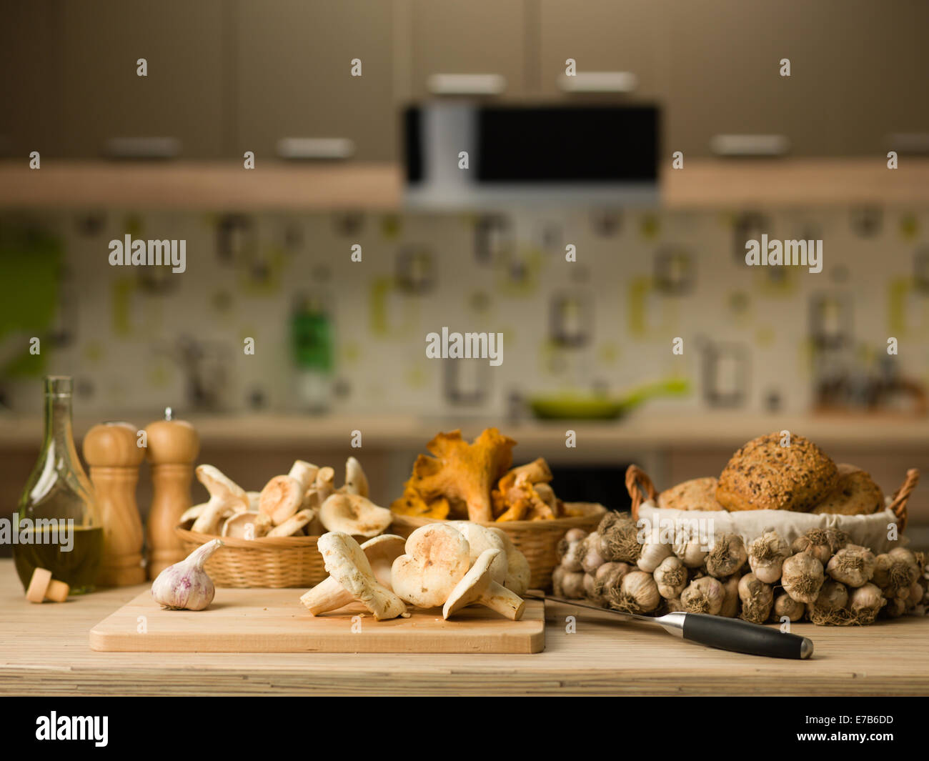 mushrooms and garlic on chopping board and baskets on table, kitchen still life - Stock Image