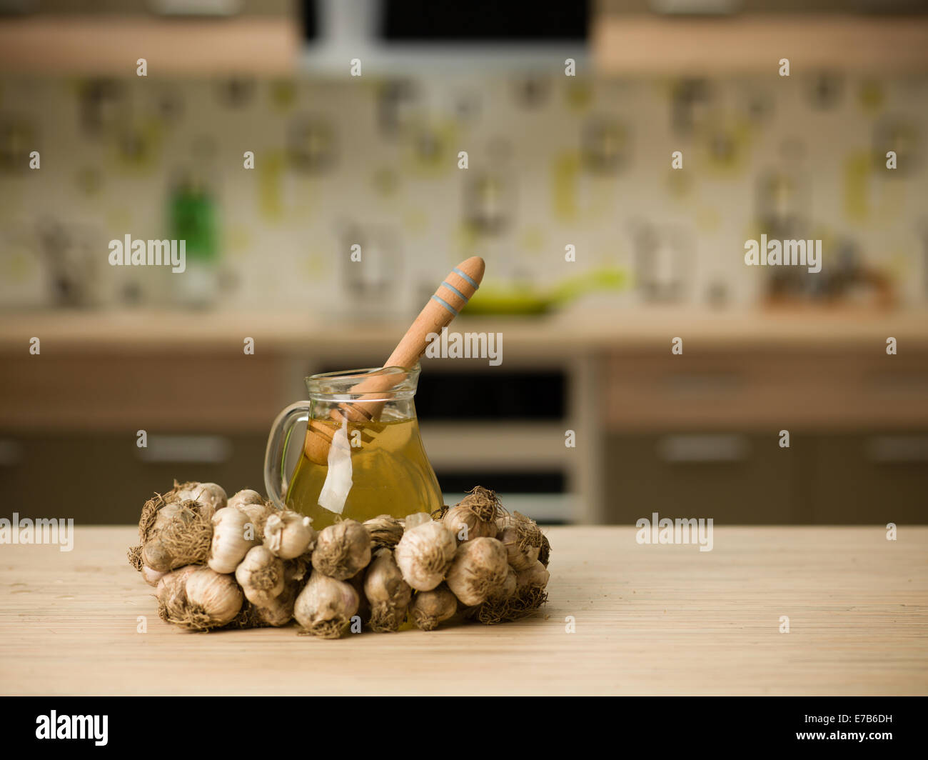 string of garlic surounding a jug with honey, on wooden kitchen table - Stock Image