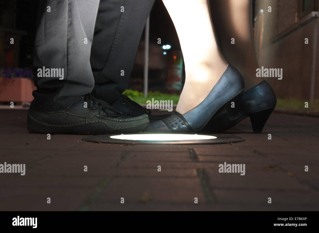 feet of man and woman near the bright lantern at night - Stock Image