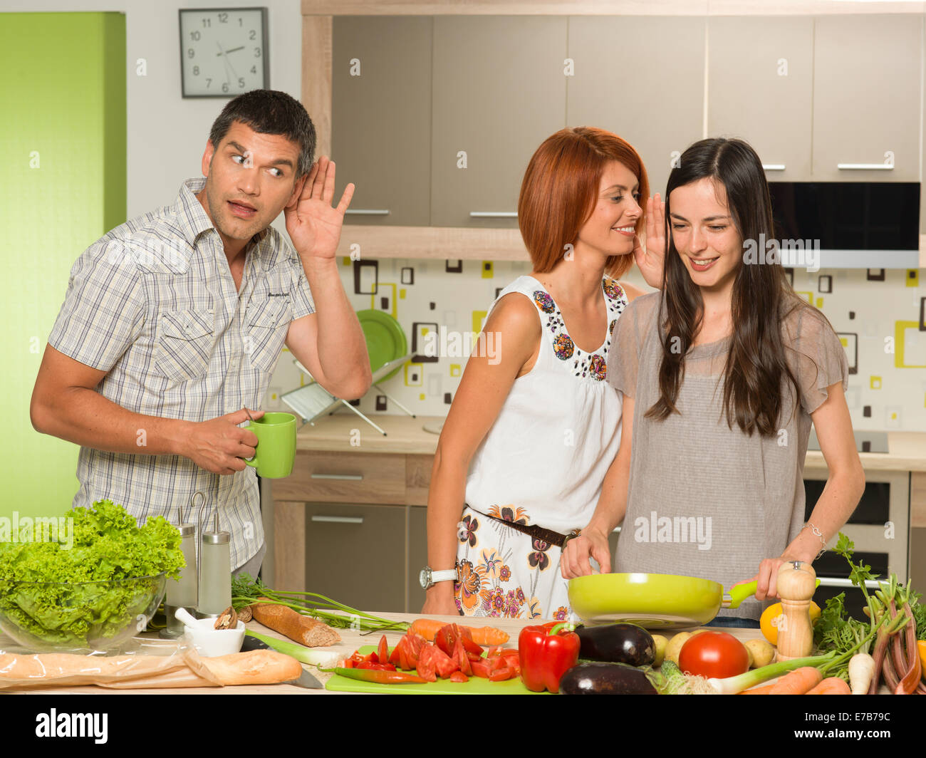 portrait of two beautiful caucasian women standing in kitchen cooking, laughing and whispering something, with one Stock Photo