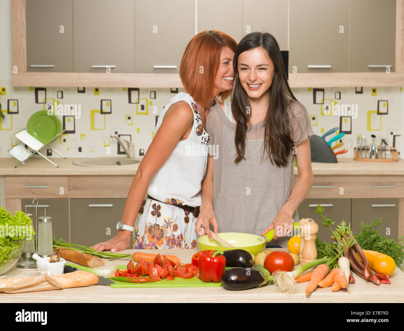 portrait of two beautiful caucasian women standing in kitchen and cooking, laughing, whispering something Stock Photo