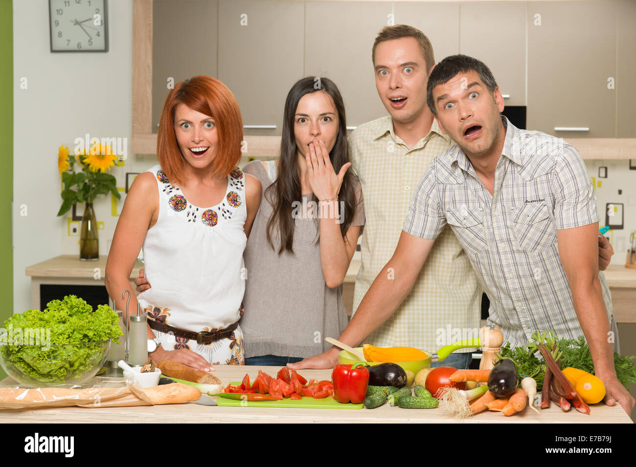 portrait of four young caucasian people standing in kitchen, table with colorful mixed vegetables, acting surprised - Stock Image