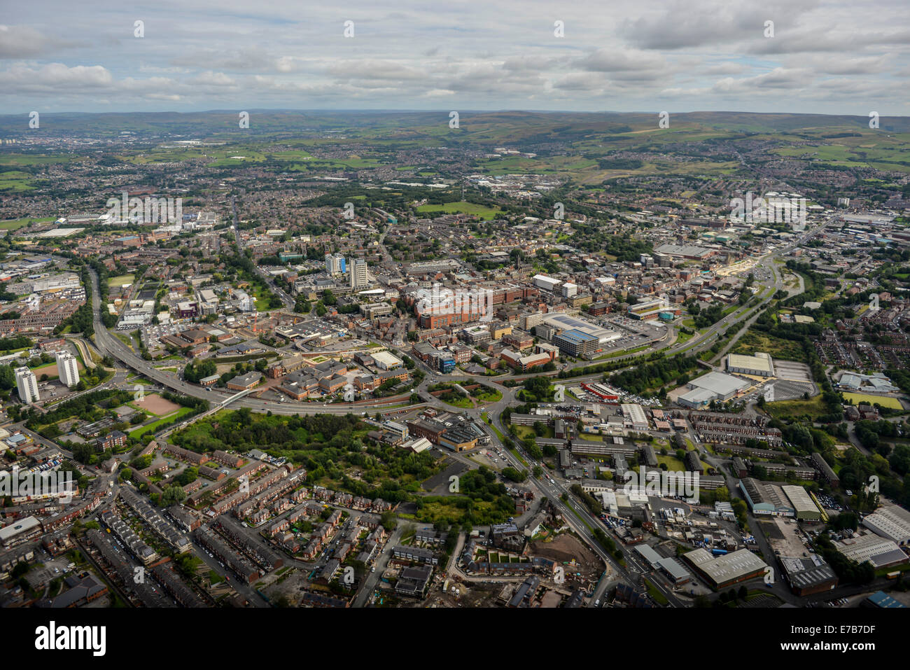 An aerial view across the centre of Oldham, Greater Manchester. Open countryside is visible in the distance. - Stock Image