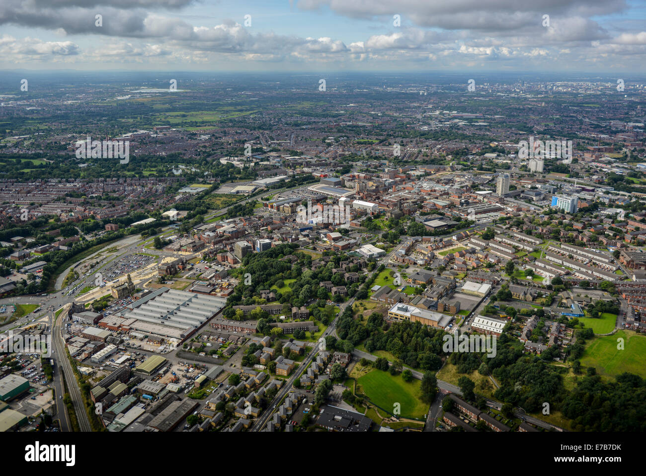 An aerial view across the centre of Oldham, Greater Manchester. Central Manchester is visible in the distance. - Stock Image