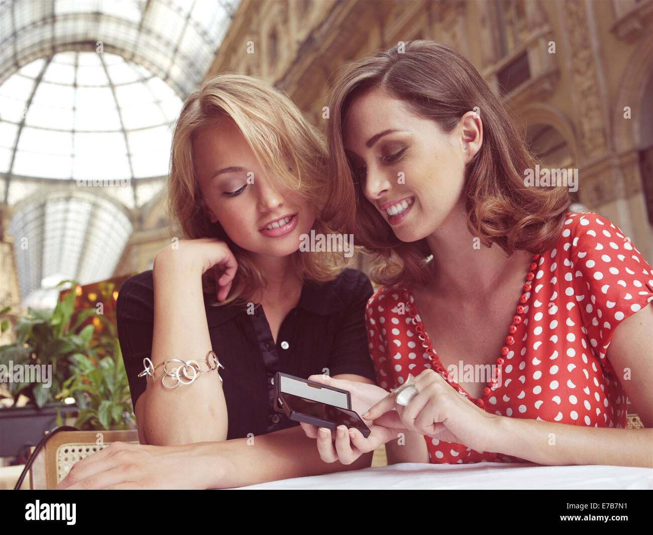 young women smiling and laughing as they look at text message on mobile phone - Stock Image