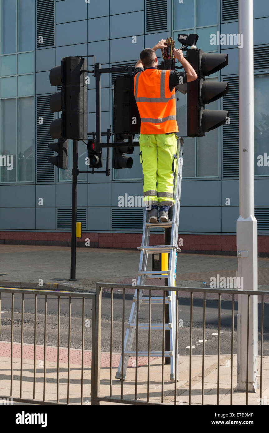Engineer fixing some traffic lights - Stock Image