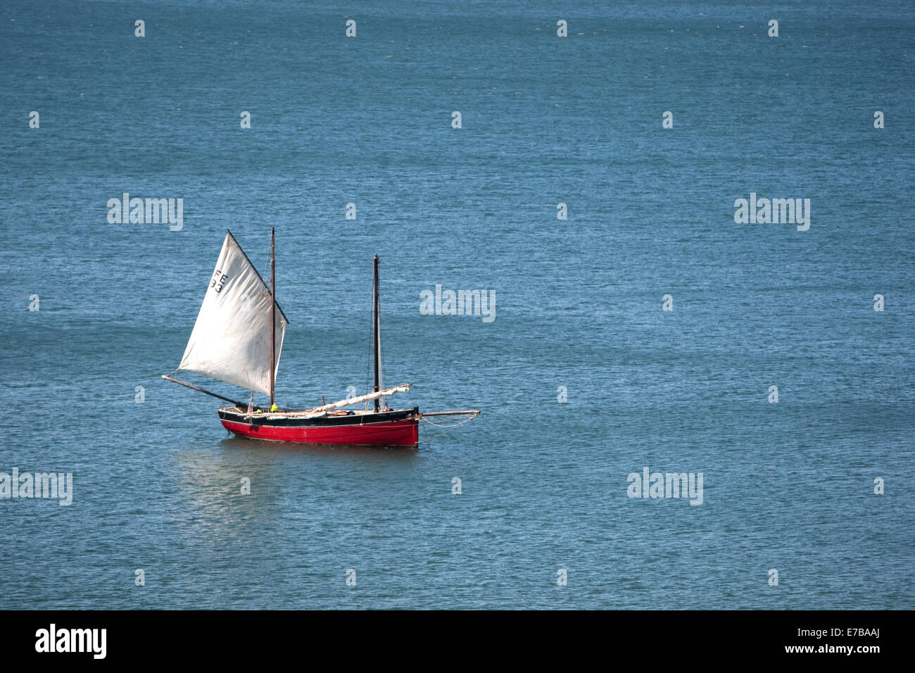A small red boat with a white sail on blue sea - Stock Image