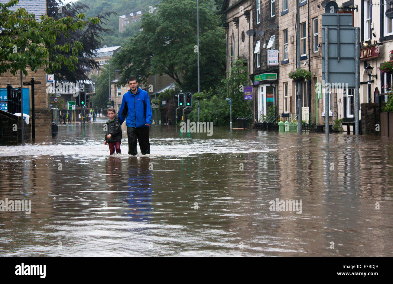 Man and boy wading through flood waters, Hebden Bridge, West Yorkshire, UK Stock Photo