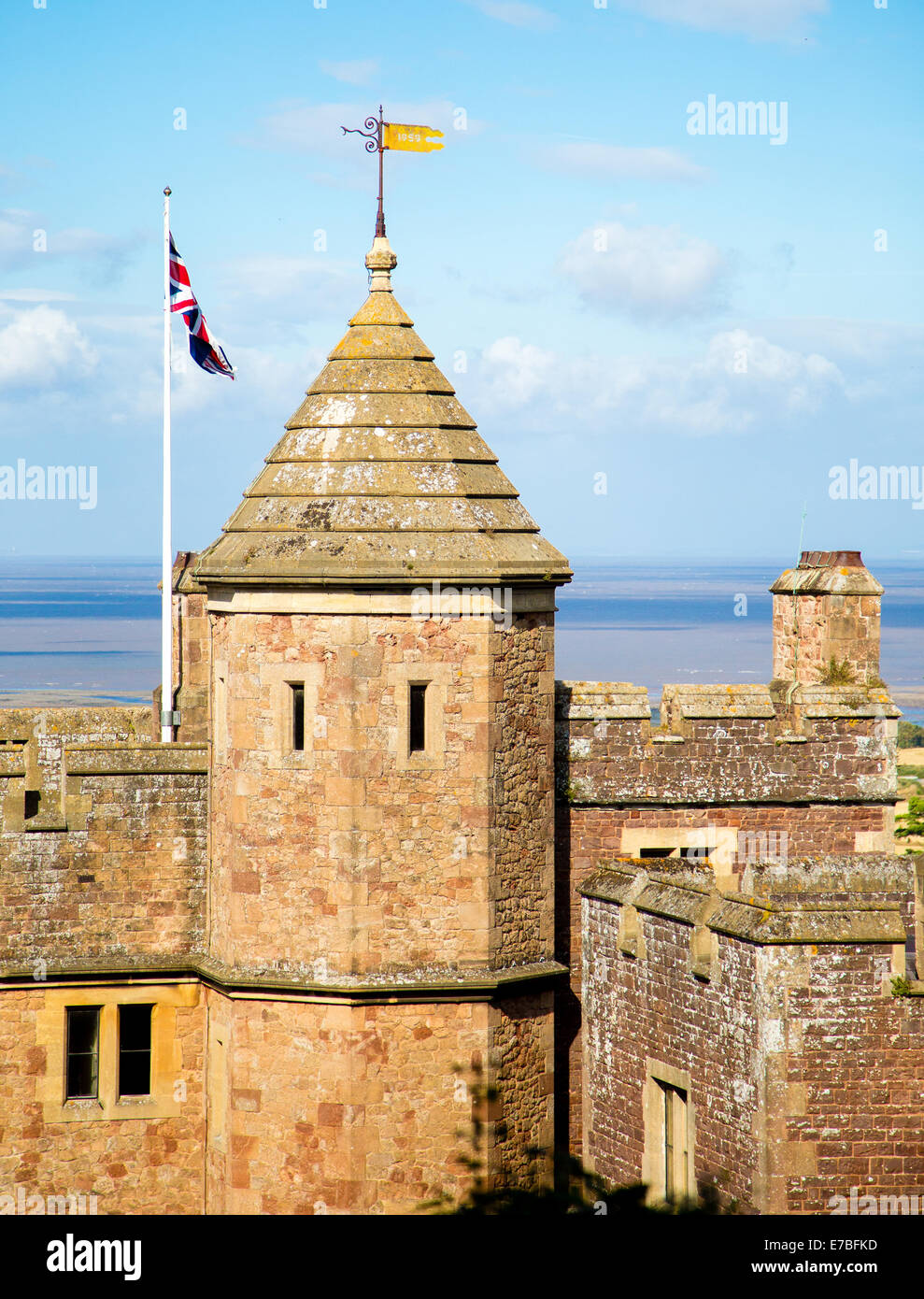 Turret and battlements of Dunster Castle in Somerset UK with the Bristol Channel in the distance - Stock Image