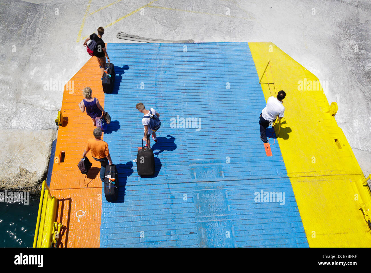 Passengers disembarking from a Greek island hopping ferry along its colourful gangplank - Stock Image