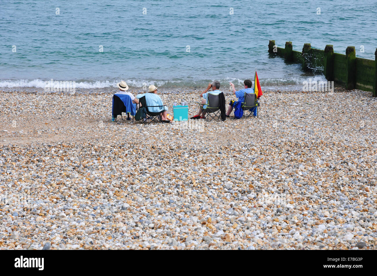four people sitting on stony beach overlooking the sea. - Stock Image