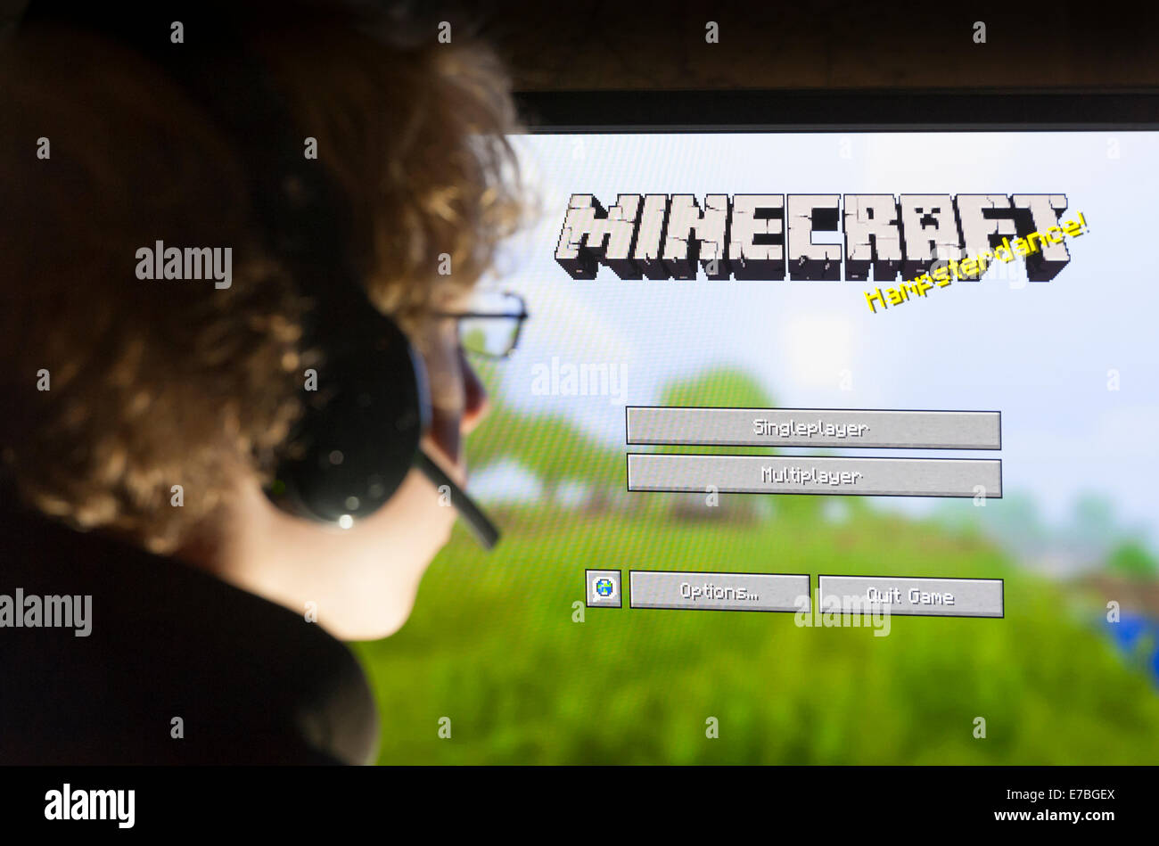 A teenage boy sits in front of his computer screen and plays the computer game Minecraft, developed by Swedish company - Stock Image