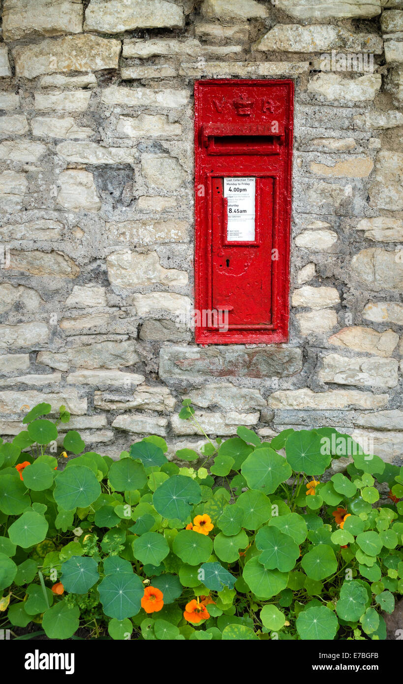 Small Victorian village postbox set into a stone wall with a border of Nasturtiums Somerset UK - Stock Image