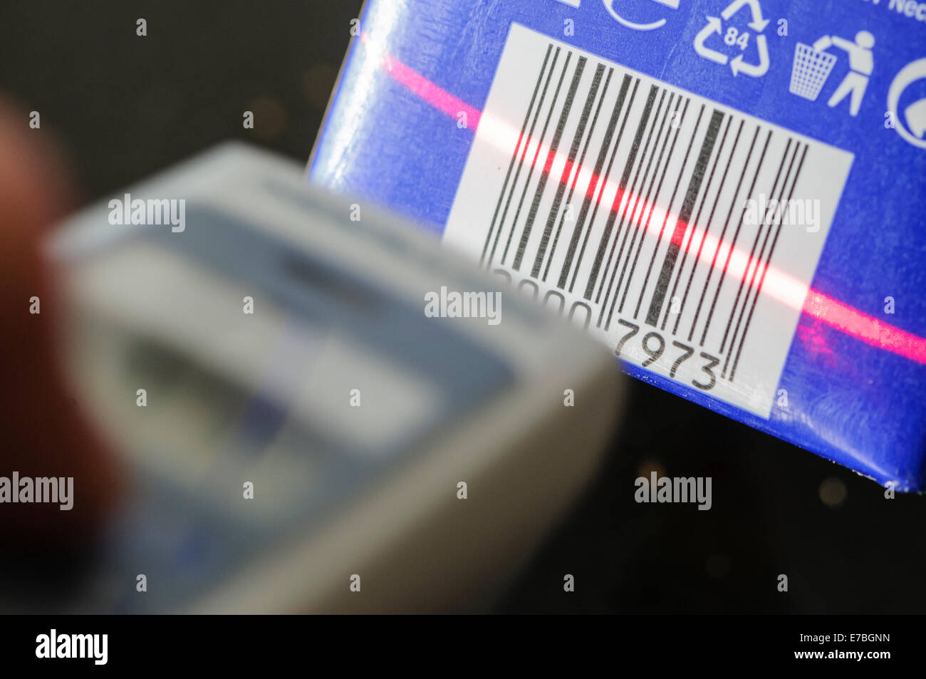 A man uses a handheld barcode scanner - Stock Image