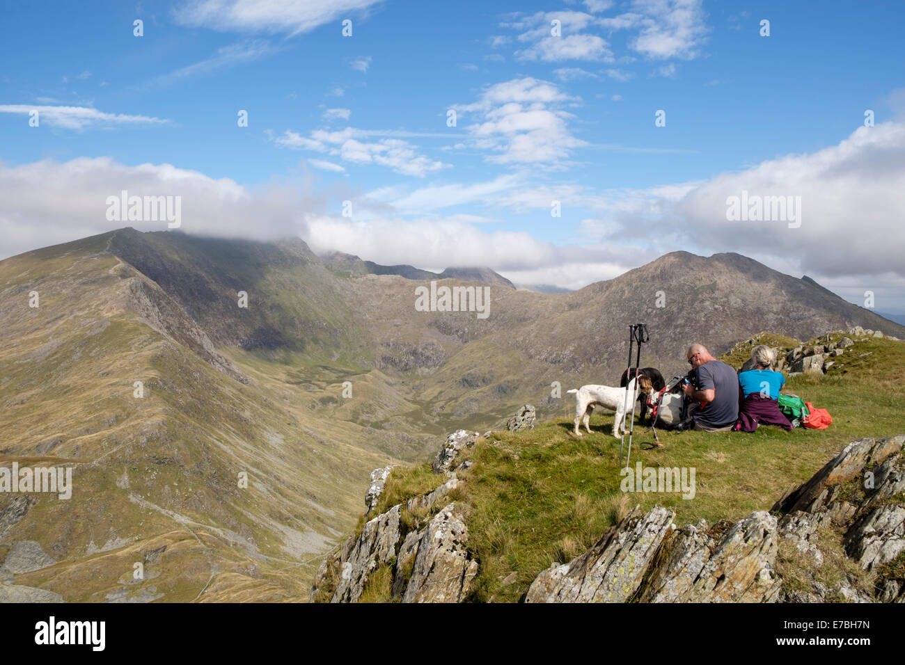 Walkers resting on Yr Aran summit with view across Cwm Llan to cloud topped Snowdon peak in mountains of Snowdonia - Stock Image