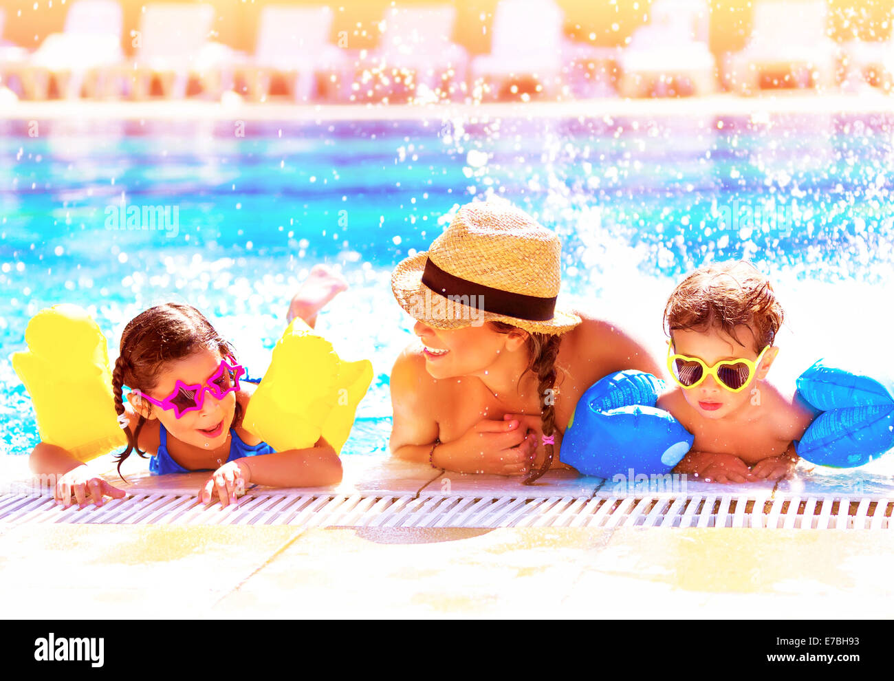 Portrait of happy cheerful family having fun in aquapark, swimming in the pool, relaxing in luxury summer resort - Stock Image