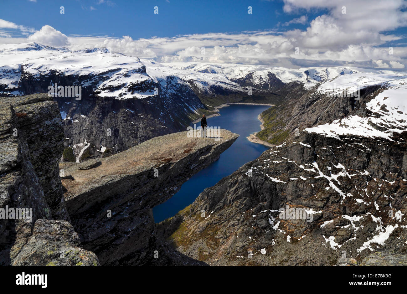Hiker enjoying the view from Trolltunga in Norway after a long trek Stock Photo
