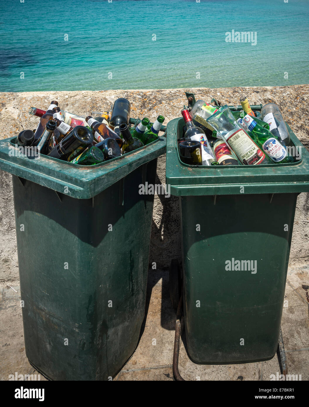 Discarded bottles of alcohol in dustbins by the sea. - Stock Image