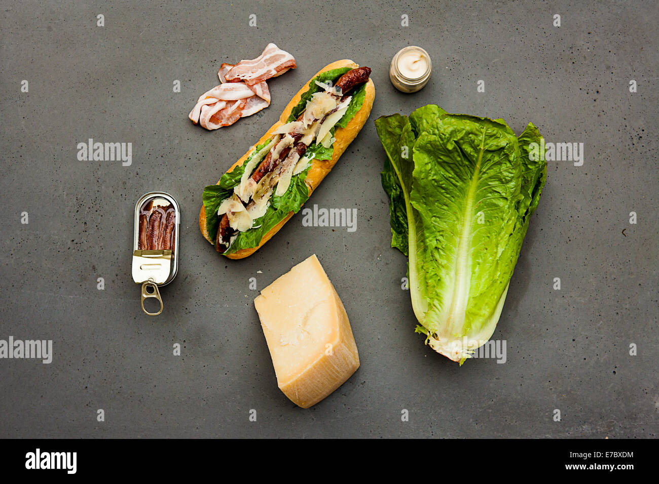 Modern hot dog with lamb sausage, bacon, parmesan, romaine lettuce, anchovies, dressing sauce on concrete table - Stock Image