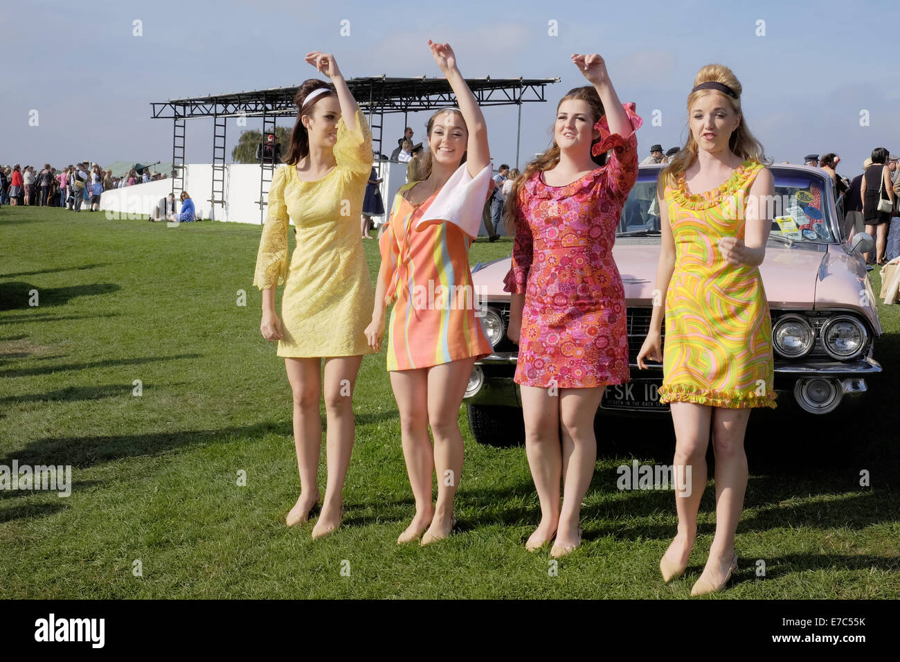 Four pretty young girls in there late teens early twenties dressed in vintage 60s fashion clothing with bright colourful - Stock Image