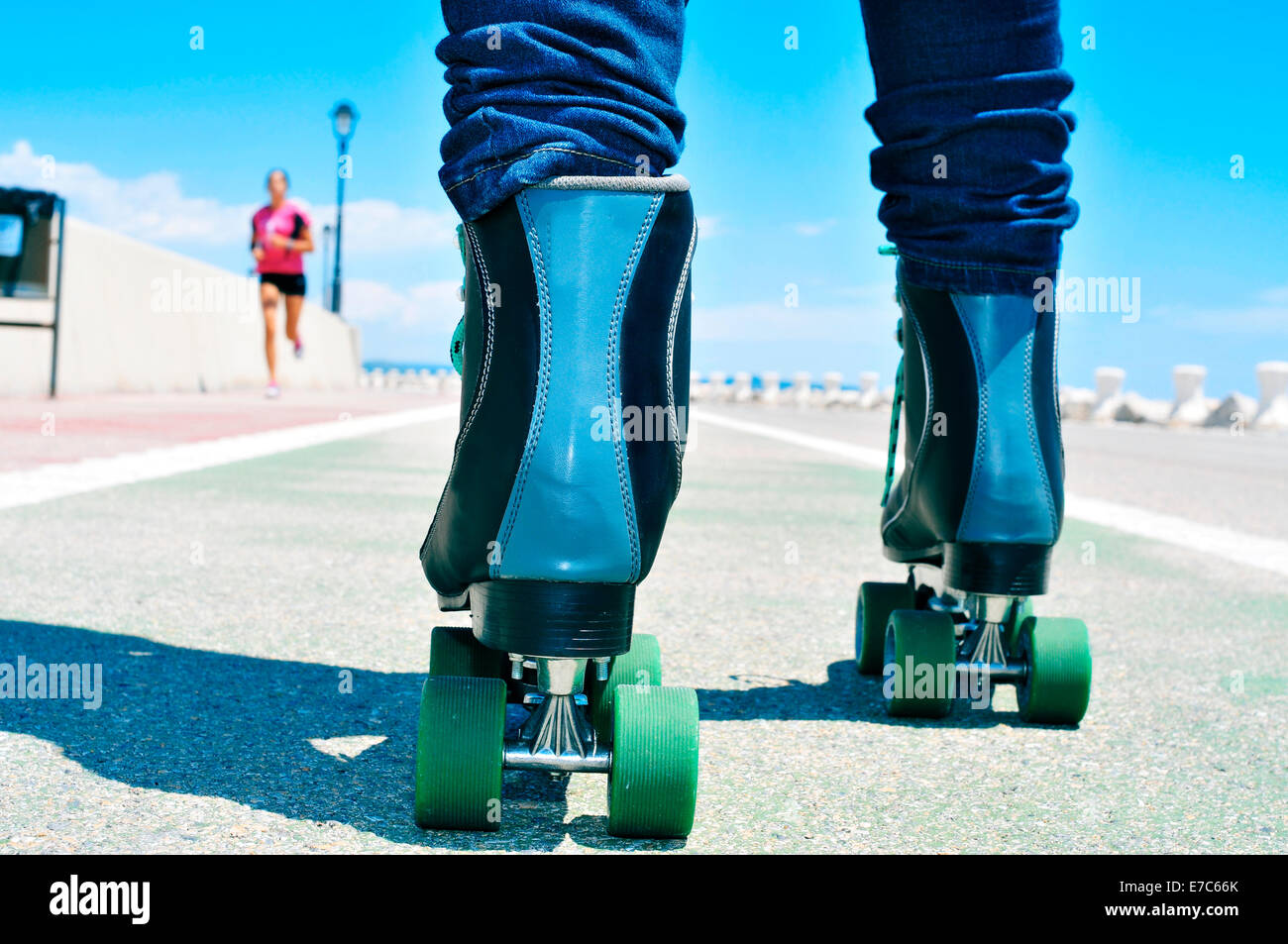 closeup of a young man roller skating on a no traffic road - Stock Image