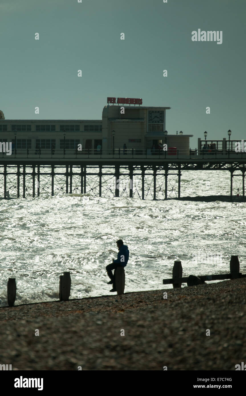 A man sits on the sea defenses at Worthing with the pier in the background - Stock Image