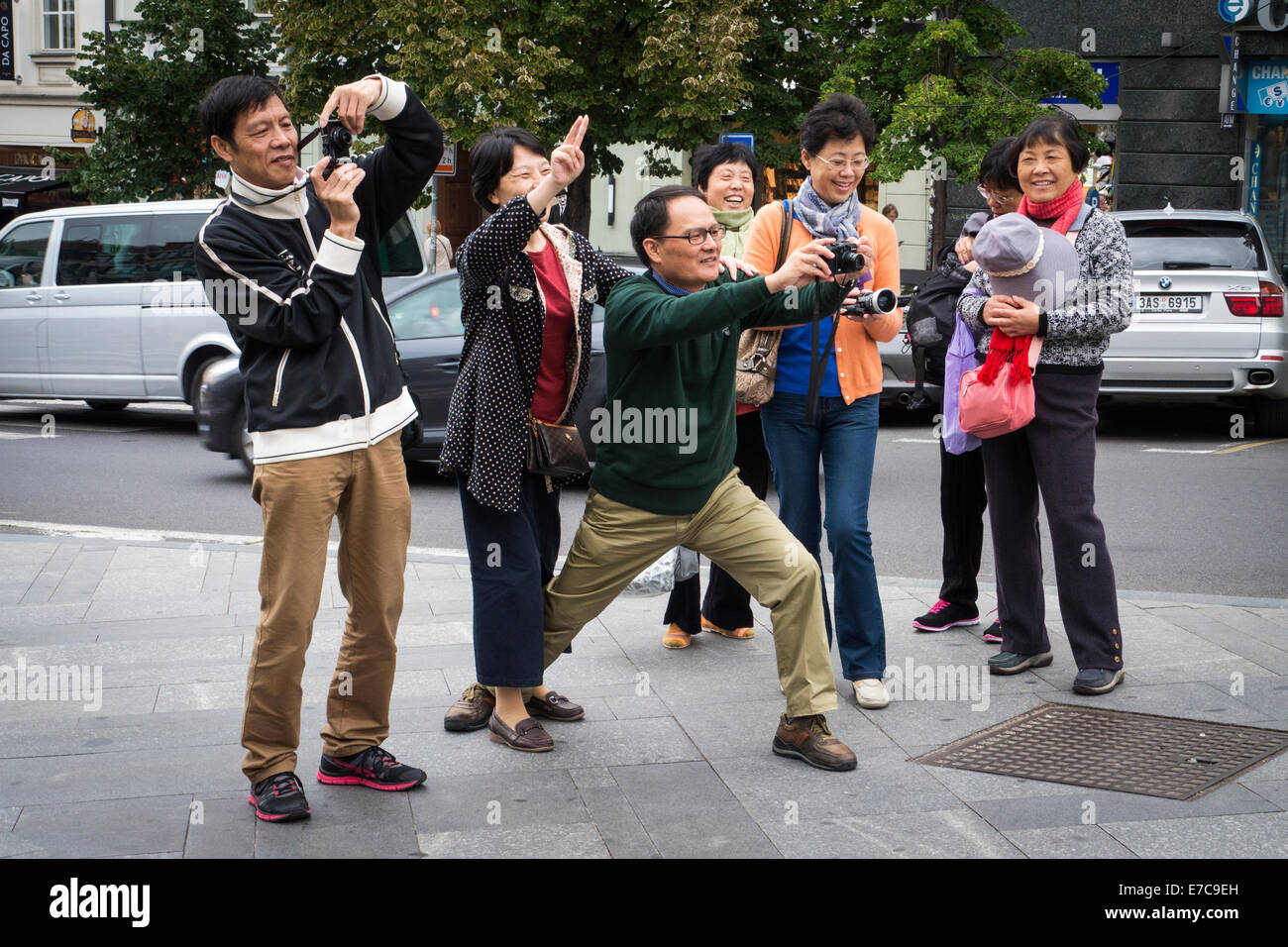 Asian tourists are taking photographs in Wenceslas Square in Prague, Czech Republic - Stock Image