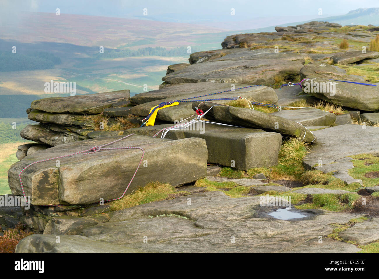 Rock climbing belay and safety anchor ropes fixed at the top of a crag on Stanage Edge in the Peak District Derbyshire - Stock Image