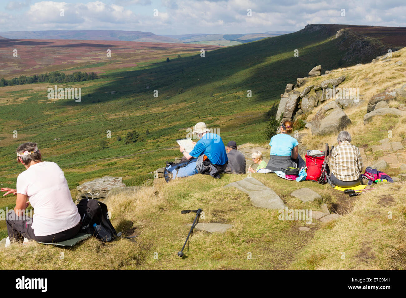 A group of walkers sitting on Stanage Edge and eating lunch Stock Photo