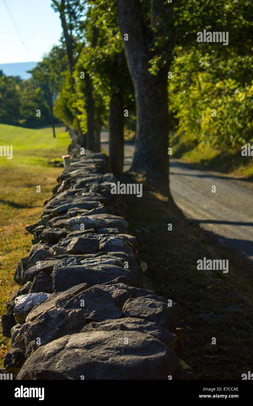 Stone farm wall along a rural gravel road. - Stock Image