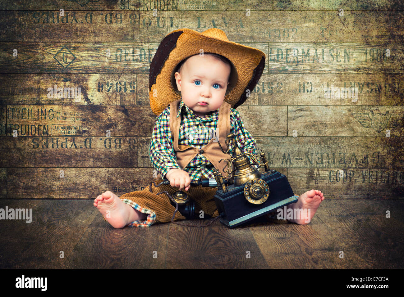 cute kid in cowboy hat with retro phone on background of boards