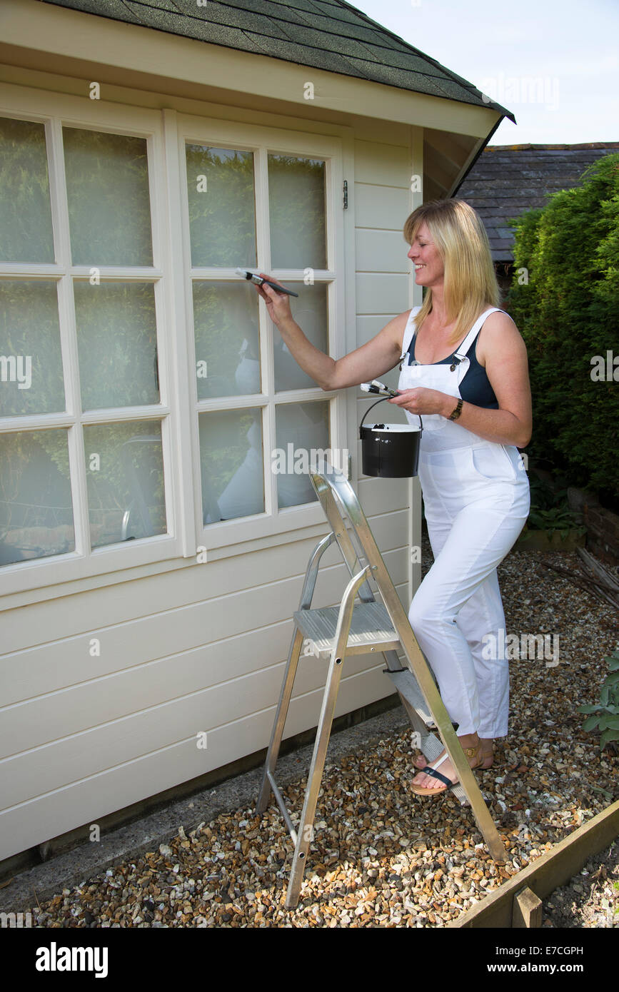 office decorator. Painter Decorator Painting Windows Of A Garden Office Standing On Step Ladder