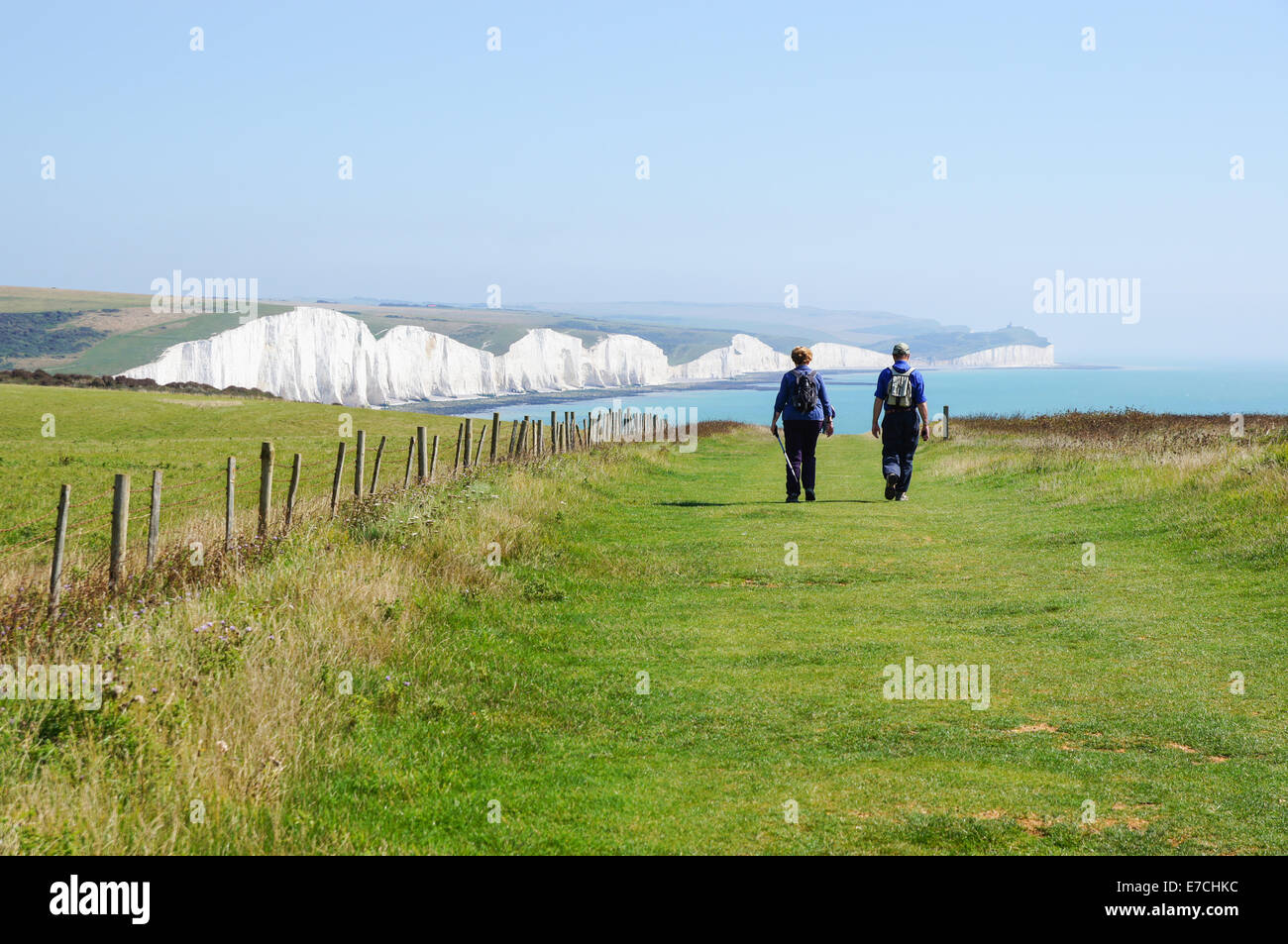 Walkers striding towards the Seven Sisters chalk cliffs near Seaford East Sussex England United Kingdom UK Stock Photo