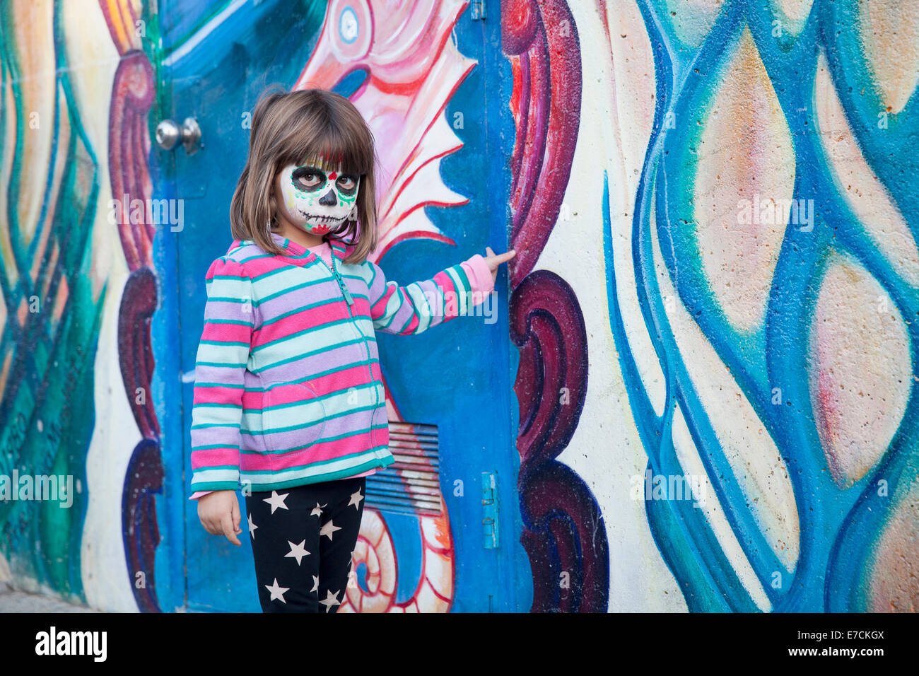 Little girl with face painted for Dia de los Muertos in front of mural, Garfield Park, Mission District, San Francisco, - Stock Image