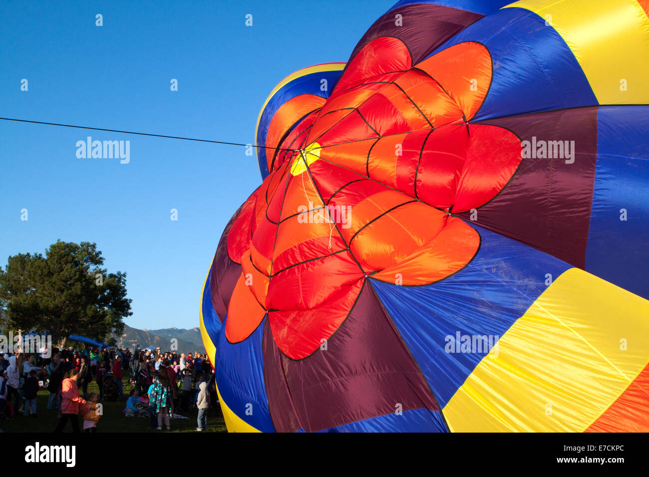 People watch as a colorful hot air balloon is inflated on the last day of the last scheduled Balloon Classic in Colorado Springs Stock Photo