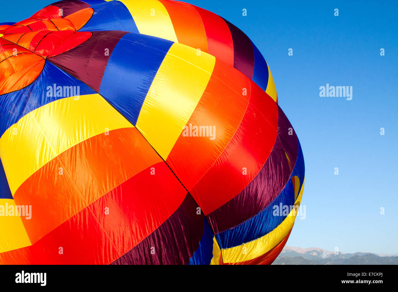 A colorful hot-air balloon being inflated with the Rocky Mountains in the distance Stock Photo