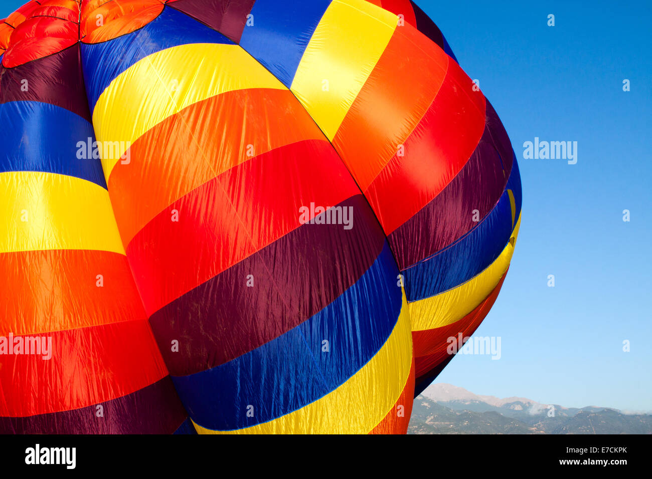 A colorful hot-air balloon being inflated with Pikes Peak in the distance Stock Photo
