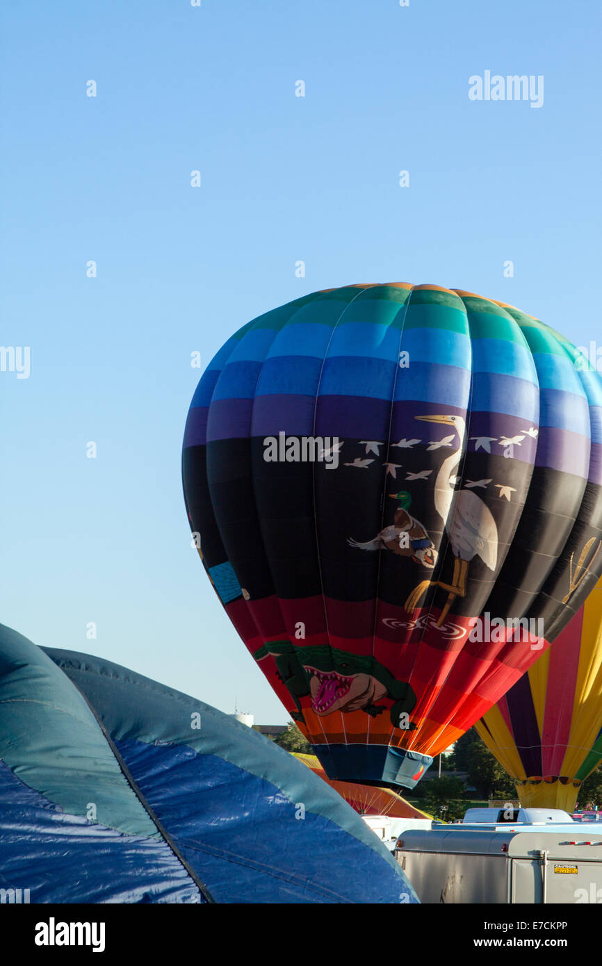 Colorful hot air balloons are readied for launch against a blue sky Stock Photo