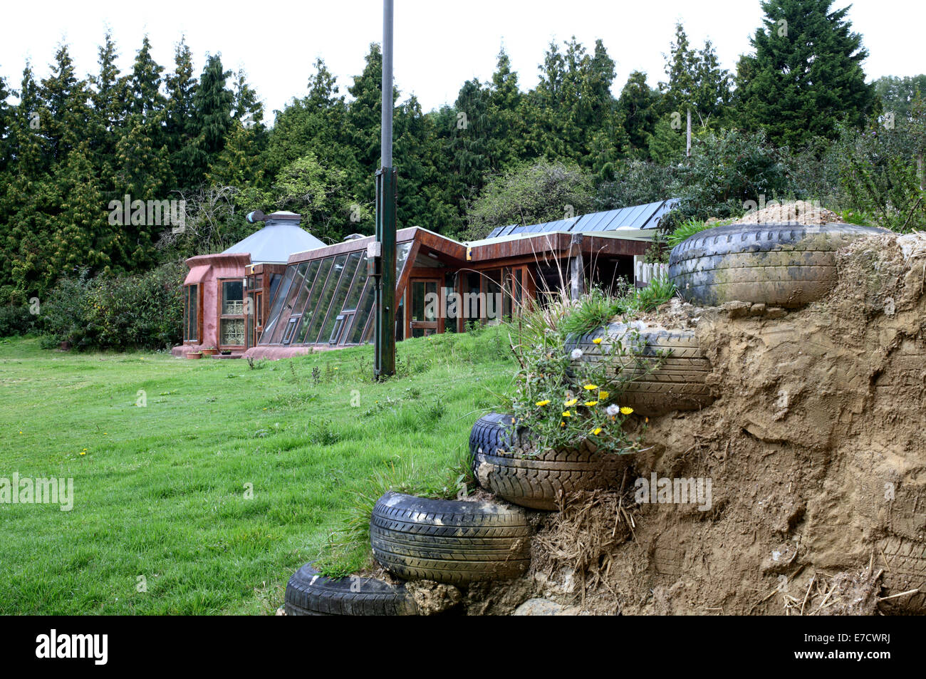 The Brighton Earthship with, in the foreground, an example of how an earthship wall is constructed of vehicle tyres - Stock Image