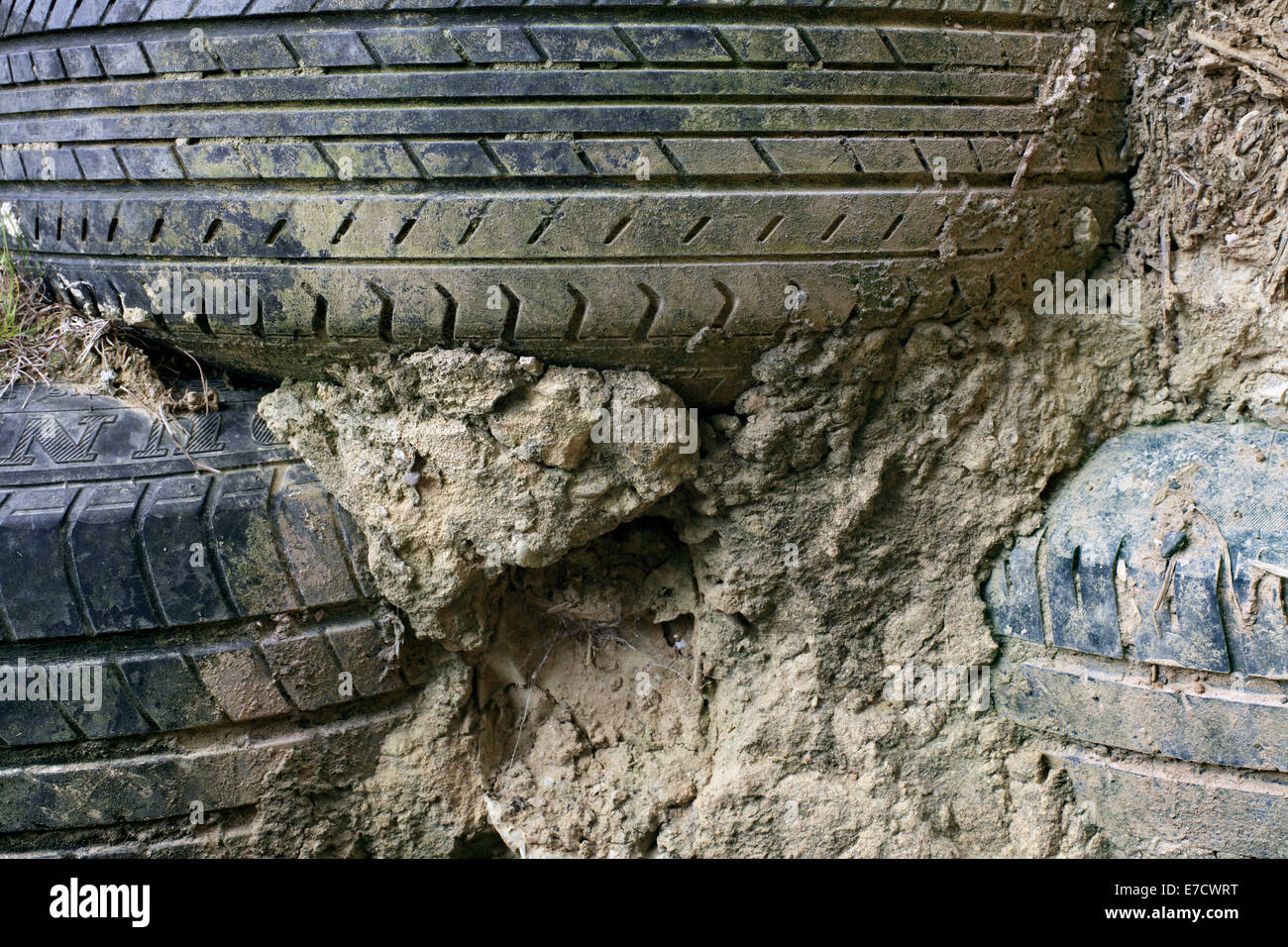Close up of used vehicle tyres and rammed earth, showing how an earthship wall is constructed. Brighton Earthship, - Stock Image