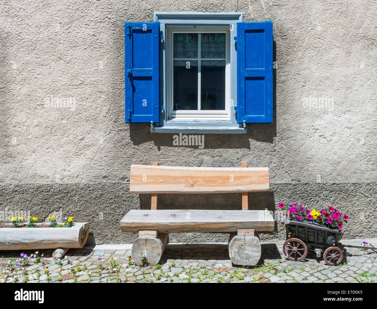 Window with shutters, wooden bench. Small truck, stylized as flower pot. Cozy  simple old times life. - Stock Image