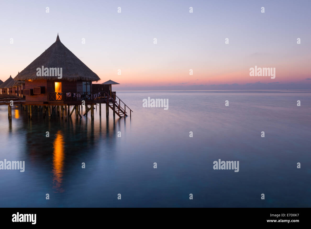 Panorama of tropical island resort with over-water bungalows at night. Maldives. Ari Atoll.  Scenic sunset over - Stock Image