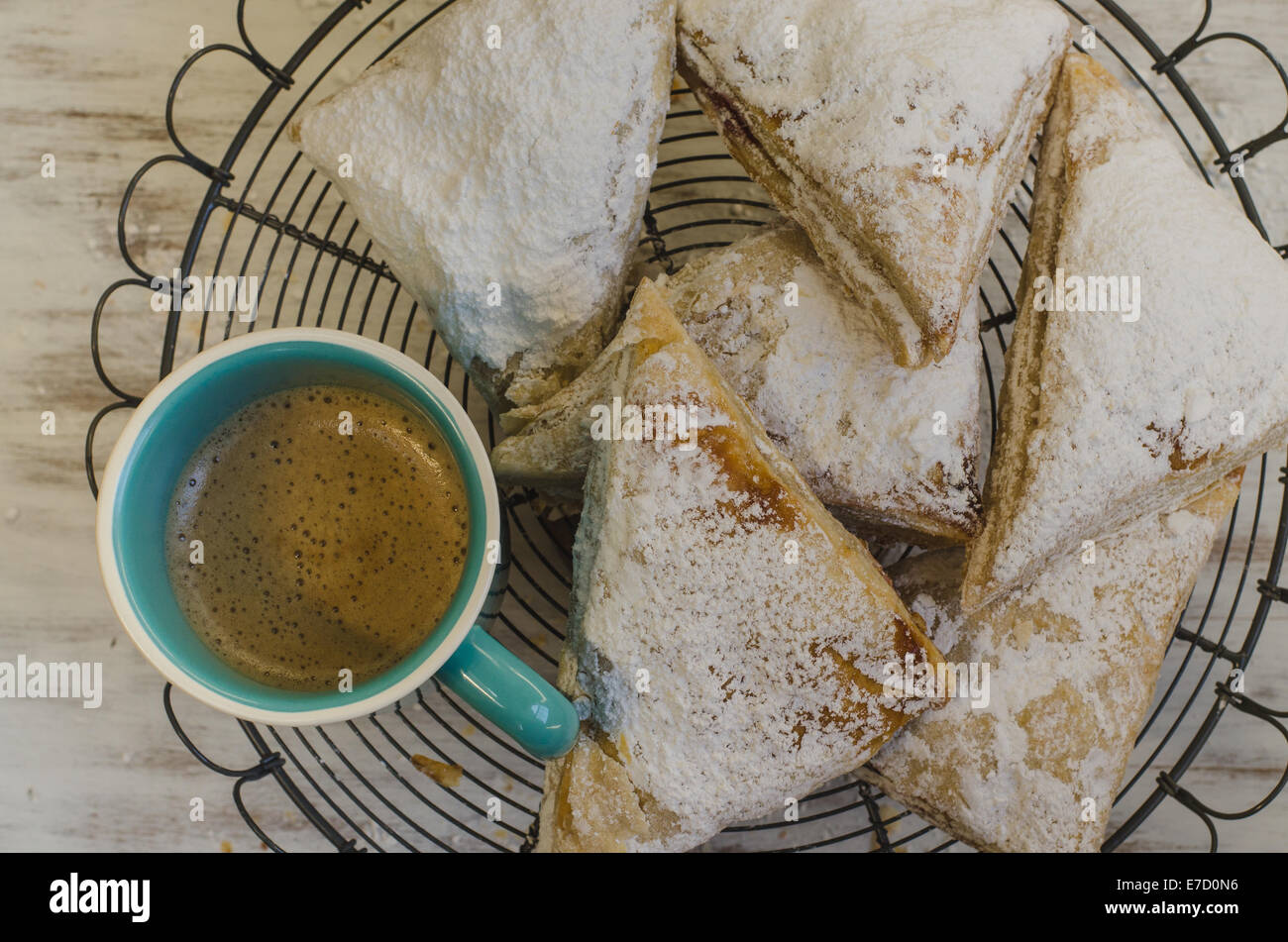 Flaky fruit turnover pastries with coffee on wire rack - Stock Image