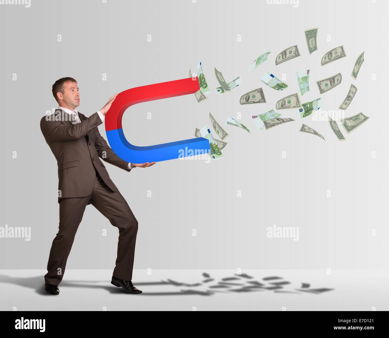 businessman in suit holding big magnet and attracts money stock