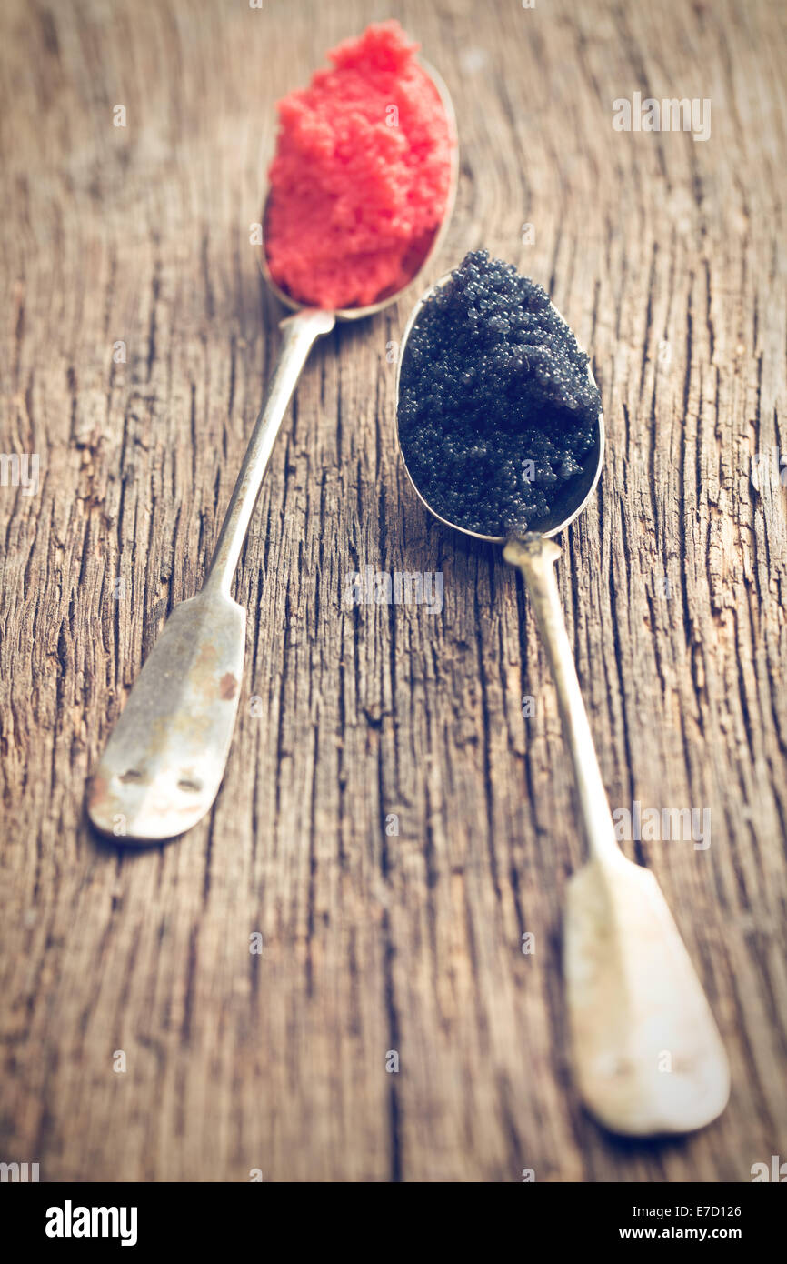 black and red caviar in spoon on wooden table - Stock Image