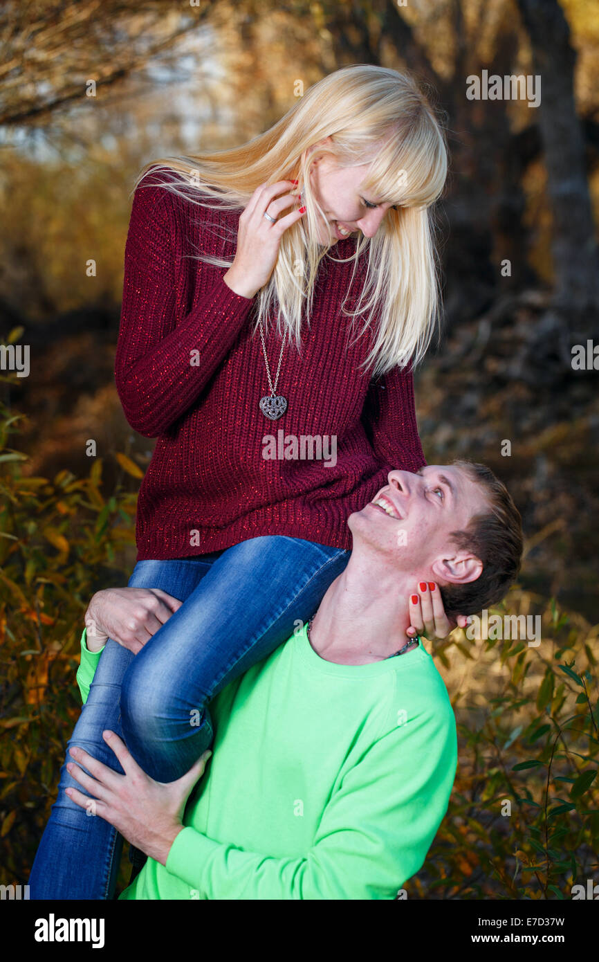 The young man put the girl to his shoulder shot in the park - Stock Image