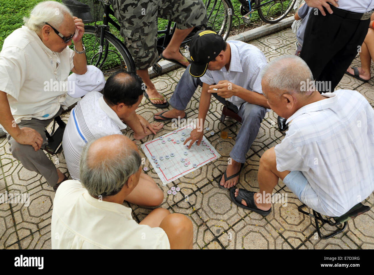 Men play a board game on a street in Hanoi, Vietnam. Stock Photo