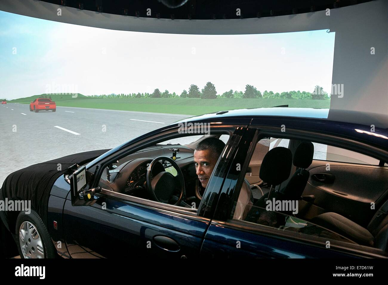 US President Barack Obama sits in the driver's seat of a vehicle simulator during a tour of the Turner-Fairbank - Stock Image