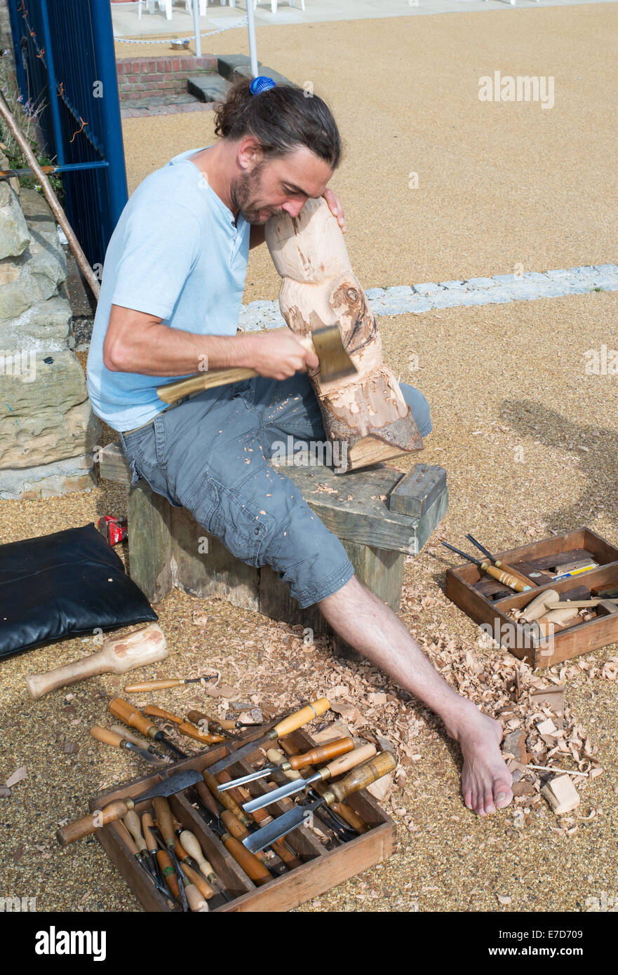 Sculptor Mark Crowley using an axe to carve a wooden Dolly or figurehead North Shields, North East, England, UK - Stock Image